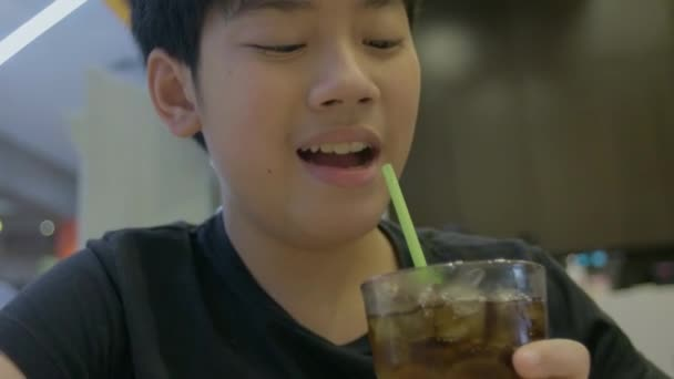 Slow motion of Teenager drinking a glass of refreshing cold fizzy cola drink with smile face.