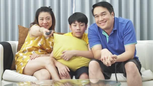 Zpomalené asijské rodiny otce matka a syn na gauči, pohled na kameru s úsměvem tvář.
