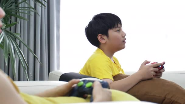 Asian mother and son playing video game at home together.4K Slow motion of happy family playing with smile face.
