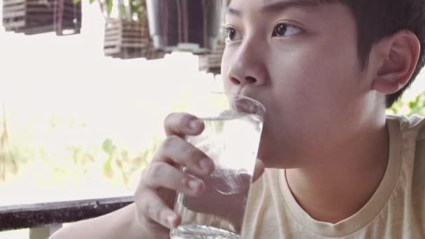 Slow-Motion der asiatische junge trinkt Wasser aus einem Glas nach dem Frühstück, teenboy mit Glas Wasser hautnah.