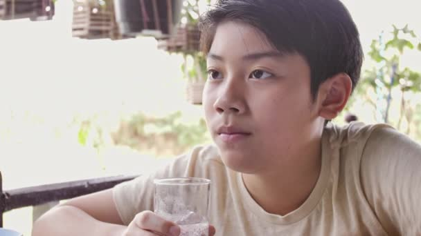 Zeitlupe von asiatischen Jungen trinkt Wasser aus einem Glas nach dem Frühstück, Nahaufnahme Teenager Junge mit einem Glas Wasser.