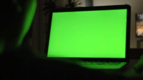 Váll nézetén gépelési, és nézni a számítógépen. Zöld képernyő technológiát használják. Chroma Key laptop.