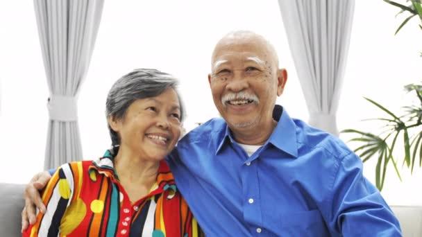 Porträt eines asiatischen Senioren-Paares, das eine Kamera mit Lächeln im Gesicht anschaut, uhd Zeitlupe, Dolly Shot.