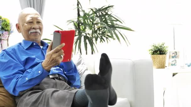 Asijské starší muž s bílými vousy pomocí tabletového počítače doma, Rozšafín stařec s technologií v ruce. Slow motion 4k, Dolly zastřelil.