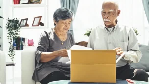 Dodávky, mail, expedice a lidé koncepce - starší muž a žena otevření pozemek box doma, 4 k zpomalené asijské starší otevřené krabice s tváří úsměv. Dolly zastřelil.