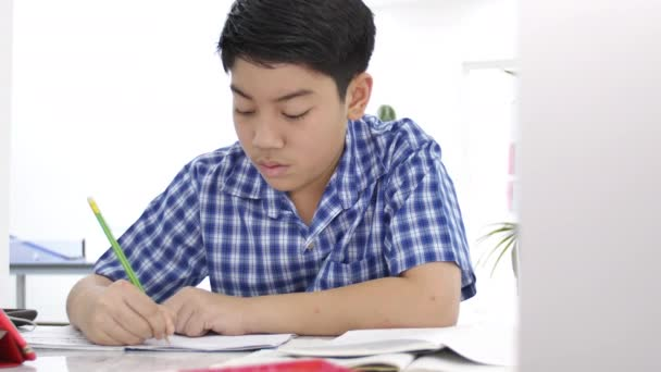 Asian cute boy doing your homework with smile face at home ,4K Dolly shot.
