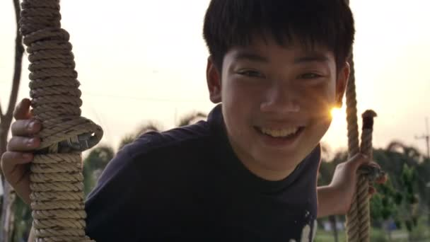 Portrait of asian child boy playing swing with sunset flare at home, Handheld Slow motion teen on swing with smile face .