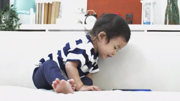 Happy asian girl play alone and watching on smart phone at home . 4K Slow motion of beautiful female child with smile face.
