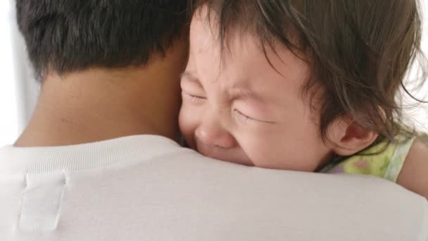 Young father soothes a crying little baby at home in the bedroom. Close-up of a little baby crying, Dad calms him down.