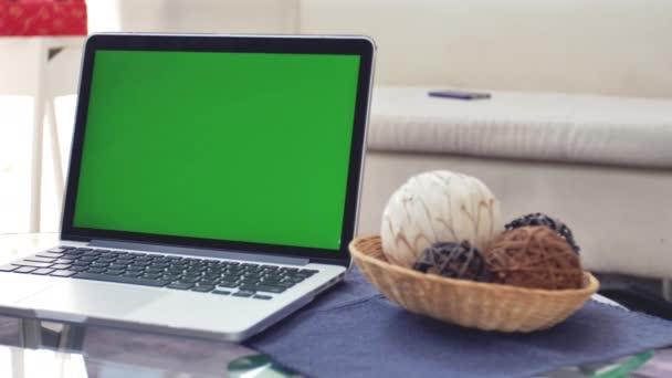 Laptop számítógép bemutatás zöld chroma kulcs képernyő áll-ra egy iskolapad-ban nappali. A háttérben hangulatos nappalijában. Dolly shot jobbról balra. 4k