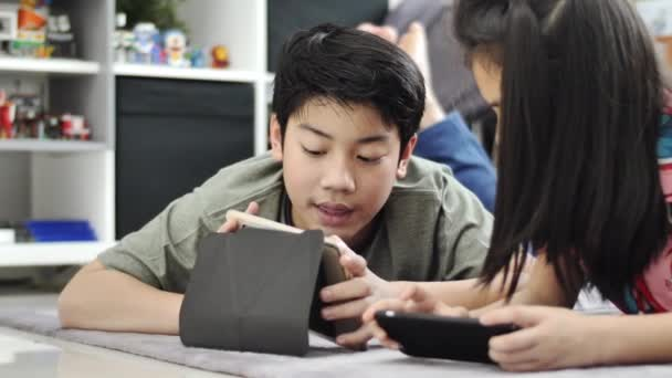 Child playing with tablet or smartphone at home , Asian boy and girl playing game on mobile phone together with smiling faces.