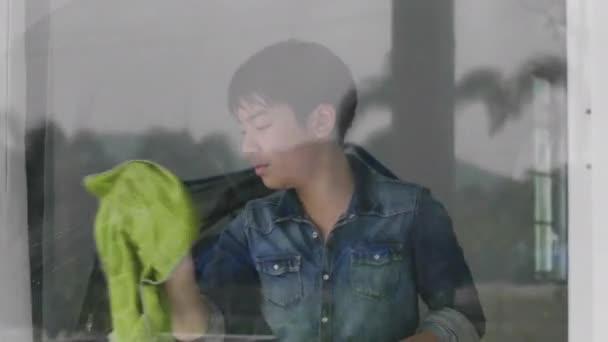 Chlapec používá skleněnou tkaninu k otření domu se šťastnou tváří, mladé asijské chlapce uklízet zrcadlo doma.