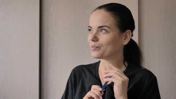 A beautiful young white girl cheerfully tells an interesting story, gives interviews in bright room, office. She has long black hair, gray-green eyes,wedding ring on her finger,blue pen in her hands.