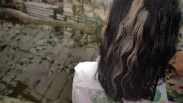 bruneta v bílých šatech sedí na proutěném křesle na kamenech, obklopeném tropickými rostlinami. Kamera směřuje shora dolů. Bílé prameny ve vlasech