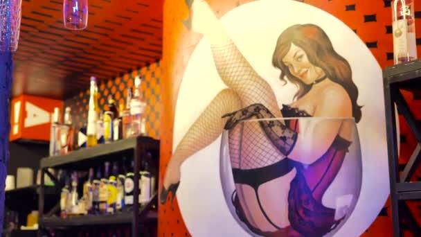 Zeichnung eines Mädchens von leichter Tugend, das in einem leeren Glas sitzt, dargestellt an der roten Wand der Bar, auf dem Hintergrund einer Vitrine mit alkoholischen Getränken
