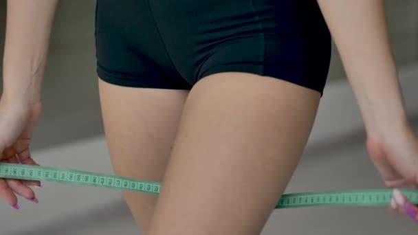 Kavkazská atletická dívka měří objem stehna pomocí měřicí pásky. Záběr zblízka
