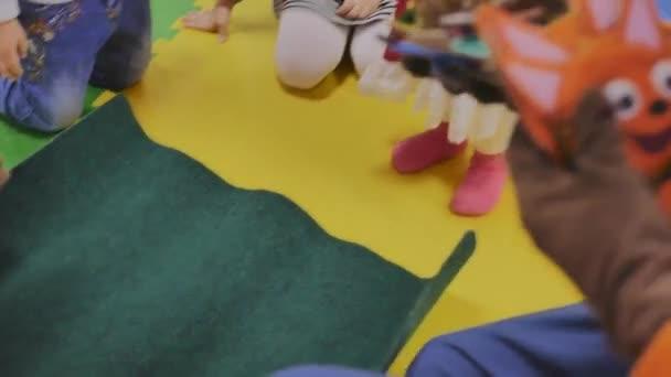 Animatoren spielen mit Kindern im Kinderzimmer in Plüschaufklebern mit Bildern, nur die Hände sind zu sehen, Nahaufnahme.
