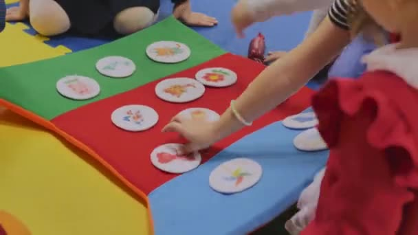 Animators play with children in the childrens room in toy plush stickers with pictures, only hands are visible, close-up.