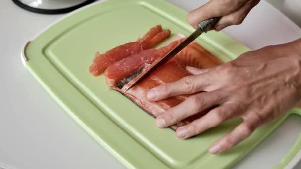 Ženské ruce ostříhat nožem a kus lososa na světle zelenou řezací desku, přírodní světlo, zblízka.