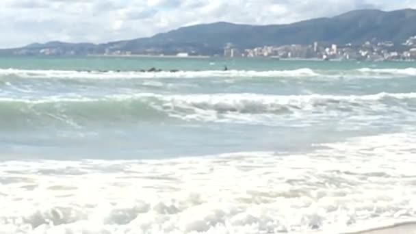 Waves crash onto rocks and breaks up on rocks on a sunny day in Mallorca, Spain