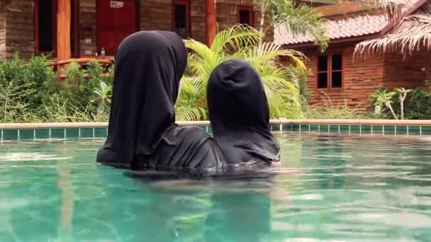 Mladá žena s kloboukem od zpátky v bazénu v exotické luxusní resort