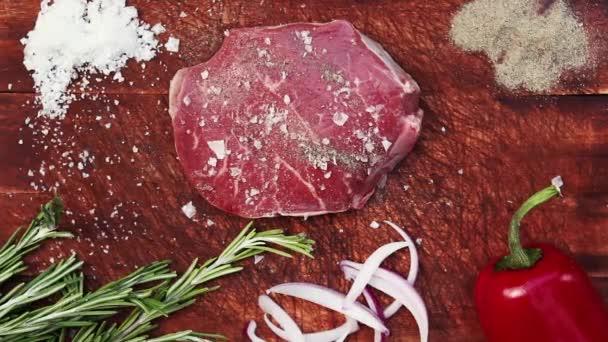 rohes Steak mit Zutaten von oben auf Holztisch.