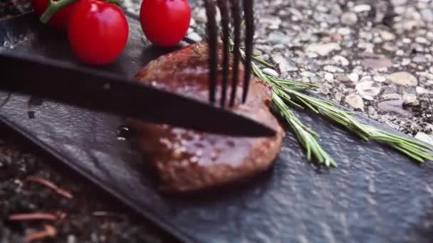 Bistecca alla deliziosa taglio su lastra scura con ingredienti freschi. Concetto di mangia culinario