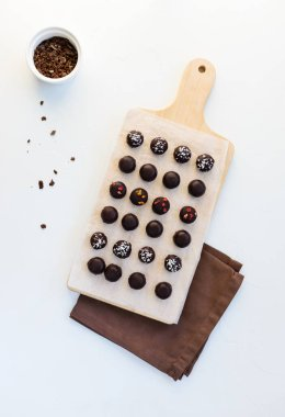Homemade sweets made from oatmeal, walnuts and raisins, coated with dark chocolate, sublimated berries and coconut flakes on a wooden board. Sugar free, gluten, lactose.