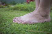 A fiatal nő mezítláb sétál a friss, zöld fűben a napsütésben