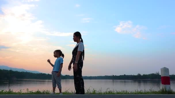 Mom holds kids stand back and looking lake on sunset. Portrait of a young family on nature, on vacation, outdoors. The concept of family holiday.