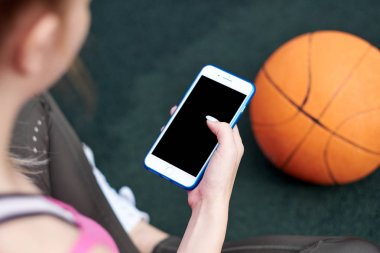 Young woman with basketball uses phone after training.