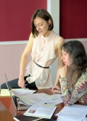 two casually dressed young ladies models sit on a desk in a vintage office and discuss model release documents, group portrait and close-up