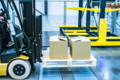 Photo Forklift yellow. Warehouse automation. The boxes are on the forklift forks. Warehousing. Logistics in stock. Forklift rides through the warehouse.