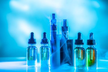 The vaping concept. Vaping set on blue background with smoke. Va