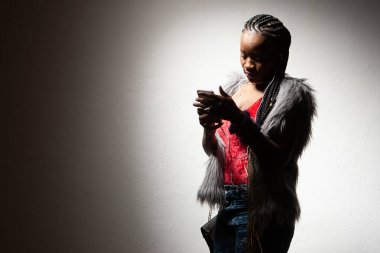 Dark-skinned model on a light background. African American woman listening to music on her smartphone. The girl listens to music. Black fashion model. African woman. Afro american girl with braids.