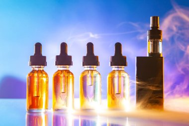 VAPE and vials of liquids are on the table. Accessories for vaping brightly lit. VAPE shop. The concept of vaping. Smoking vape. Electronic cigarette.
