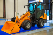 Backhoe loader. A small excavator is in the hangar. Loading equipment. Equipment for work in the warehouse. Yellow excavator in a building. Sale of street cleaning equipment.