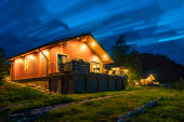 Photo Vacation home. Wooden cottage. Night illumination of a country house. House in the taiga. Concept - a home away from the hustle and bustle of the city. Scandinavian style cottage. Northern nature.