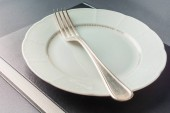 White plate with a fork lies on a thick black book