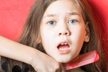 Frightened girl holding a comb at the throat on a red background