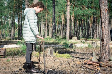 Girl with curls in light down jacket near burned out bonfire and stick for bowler hat in forest hike.