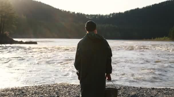 man beard mustache raincoat is standing near a river with a bucket
