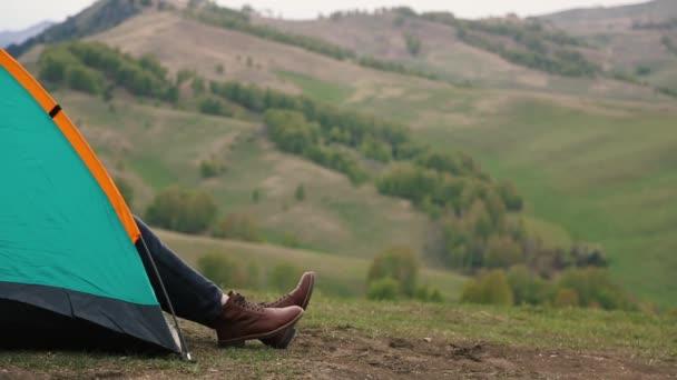člověk ráno vyhlíží ze stanu na vrcholu hory