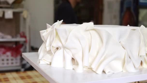 Žena kuchařka v cukrárně dokončovací dekorace na bílém fondánu dort