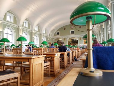 SAINT-PETERSBURG, RUSSIA:Reading room of the Russian national Library of St. Petersburg. Beautiful green lamps stand on wooden tables. People read books at May 12.2019