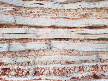 Beautiful multi-colored rock pattern. Wavy asymmetrical layers of limestone rocks. Can be used as texture and abstract background