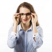 Portrét mladé ženy v brýlích oblečený v modré košili pózuje na bílém pozadí