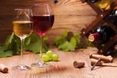 Brýle červené a bílé víno, podávané s hrozny na dřevěné pozadí