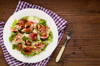 Fresh salad with figs and prosciutto with parmesan cheese and toasted almonds. Top view.