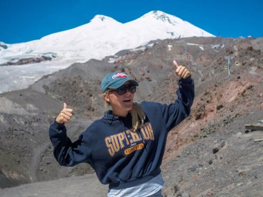 Kabardino-Balkar Republic. Russia. August 15, 2019. A young girl in a baseball cap and sunglasses on the side of Mount Elbrus in the summer. She is delighted to find herself in such a unique place. stock vector